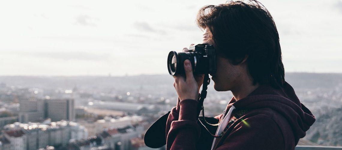 Mann mit Kamera auf Hochhaus